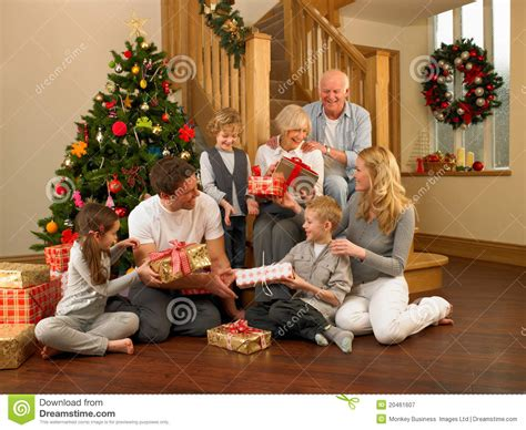 family exchanging gifts in front of christmas tree stock
