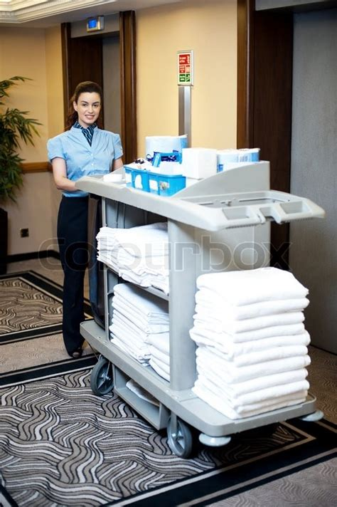 an active worker pushing housekeeping cart around the lobby stock photo colourbox