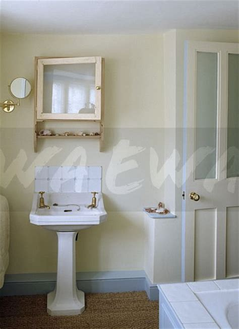 skirting board bathroom image white pedestal basin below mirrored pine cabinet in cream bathroom with pale blue