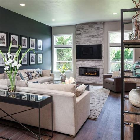 living room with big windows the accent wall fireplace and custom wood floors add