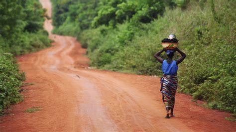african woman walking on dirt road in benin