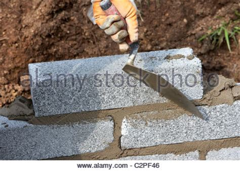 bricklayer building a wall laying half cement