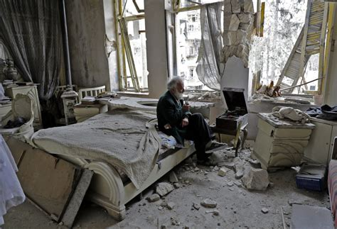 war in your bedroom photo of a syrian man listening to records in his bombed