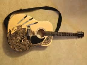 il fait de l sur sa guitare acoustique avec un crayon