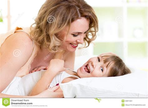 mother playing with son on bed in bedroom stock photo happy family kid with mother play laugh and stock photo