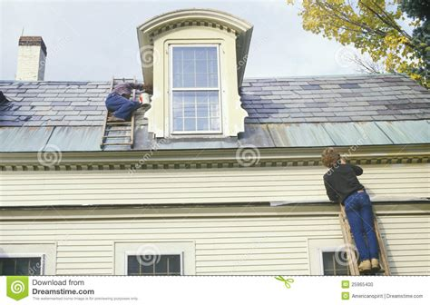 their home a couple on ladders painting their home editorial image