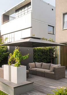tuin met vijver vlonder en overkapping strakke moderne tuin witte bloembakken houten vlonder