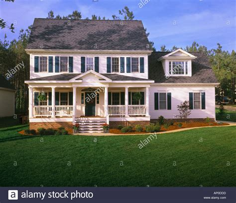 white house with blue shutters large white two story house with blue shutters a front porch and stock photo royalty