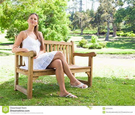 bench sitting woman with her legs crossed sitting on a bench royalty