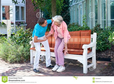 bench assistant care assistant tending to a senior lady stock image