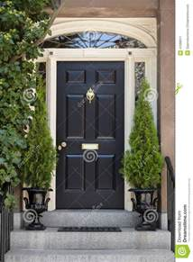 Colonial Homes Decorating Ideas black front door with white door frame and greenery stock