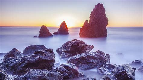 wallpaper 4k rock seaside rocks at sunrise 4k wallpapers