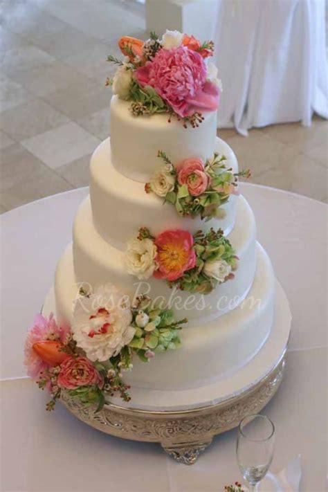 white wedding cake with cascading fresh flowers bakes