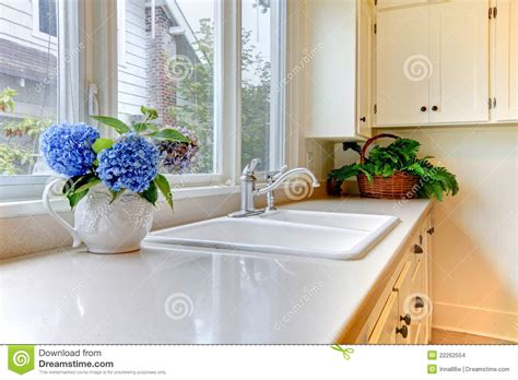 White Flower Kitchen by Kitchen Sink With White Cabinets And Flowers Stock Photo