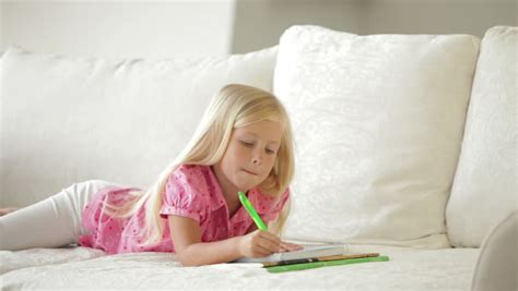 little couch cute little girl lying on couch writing in notebook and