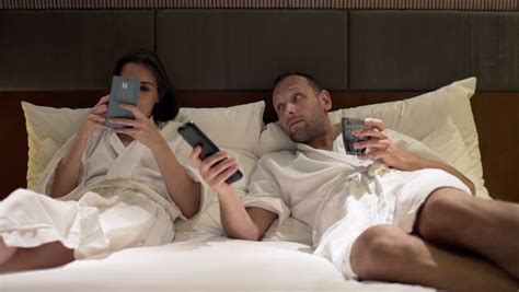 watching tv in bed young couple fighting arguing lying in bed at night stock