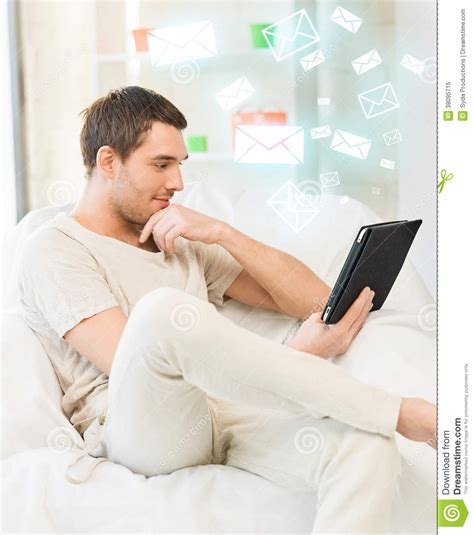 sitting on the couch man sitting on the couch with tablet pc royalty free stock