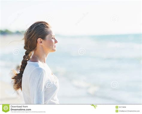 calm young woman looking into distance at seaside royalty