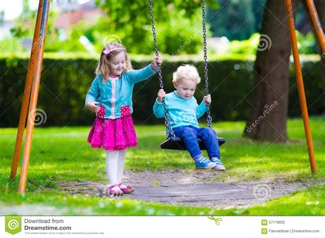 a child swings on a playground swing kids on playground swing stock photo image of play