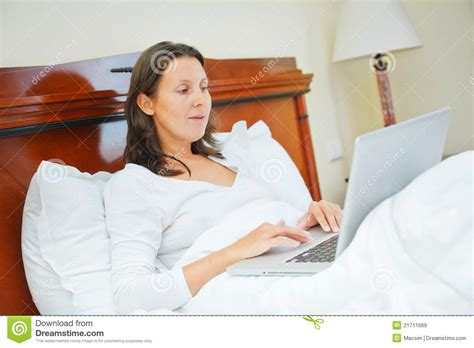 laptop in bed smiling woman using laptop sitting in bed royalty free