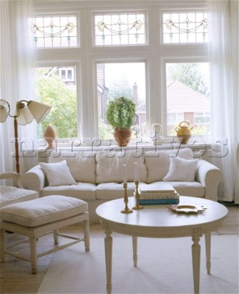sofa in front of bay window loveseat in front of wind batar