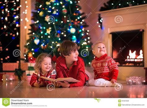 kids playing at fireplace on christmas eve stock photo