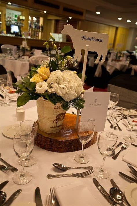 Farm wedding centrepiece. Tree slice, wooden cow with