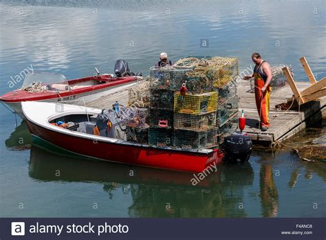 floating boat images fishermen loading lobster pots on to small boat from a