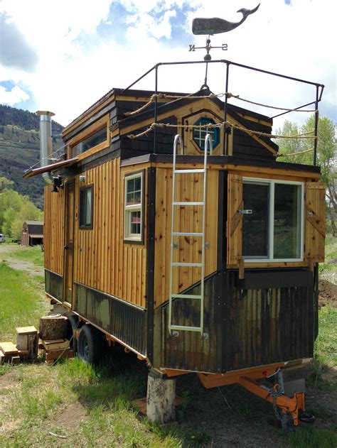 tiny house with custom tiny house features hobbit door to a balcony curbed