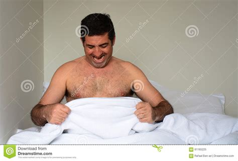man and woman sexuality in bedroom happy man in his forties 40s in bed looking down at his