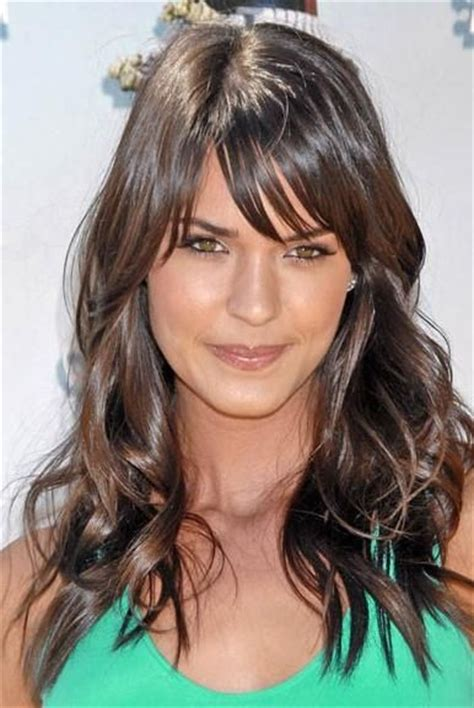 dark brunette bob haircut with wispy bangs and tucked effortless and elegant long layered haircuts with bangs