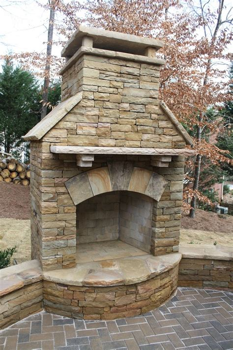 backyard stone stacked stone outdoor fireplace with seating wall and herringbone paving pattern