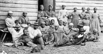 Group of slaves including men women and children gathered outside a