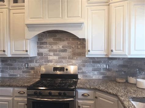 kitchen brick backsplash plain white wooden kitchen cabinet brown and black smooth rock countertop steel stove with oven