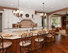 Large open kitchen features immense island done in natural wood tones