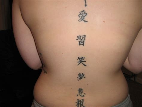 chinese symbols tattoo gracing the back in a straight line