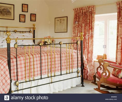 red country bedroom red checked bedlinen on antique brass bed in country