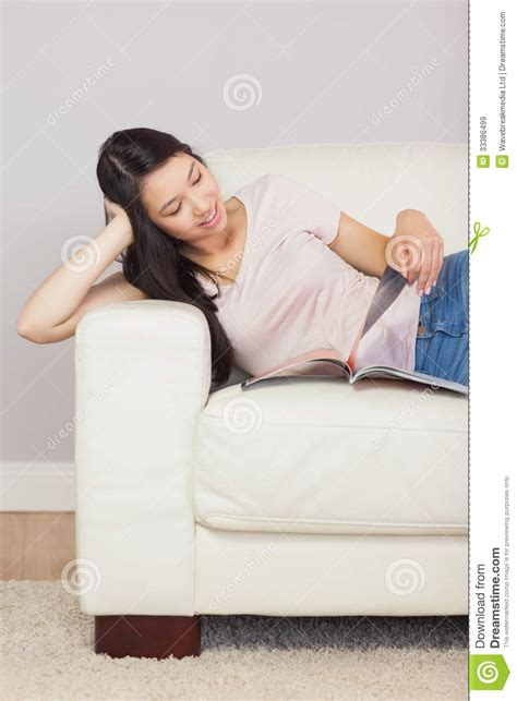 girl on the couch cheerful asian girl lying on the couch reading a magazine