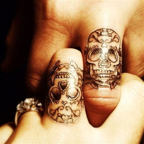 black and white finger tattoos of sugar skulls worn by