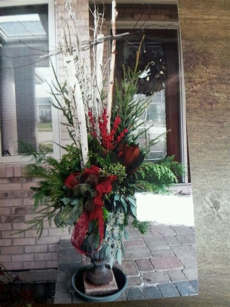 christmas decorating huge stone urns in front of entrance outside mix greens birch branches a floral affair by mazzeffi