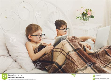 boys in bed two boys play at laptop and tablet with dog in bed stock photo image 70055150