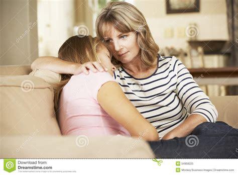 mom on sofa mother comforting teenage daughter sitting on sofa at home