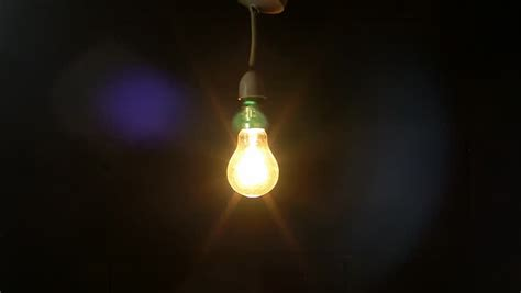swinging light abstract swinging light bulb in dark room stock footage