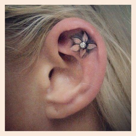 flower tattoo in ear with piercing cute ear tattoo tattoos i want pinterest so cute