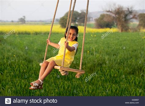 sitting on a swing girl sitting on a swing stock photo royalty free image