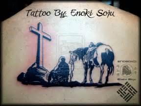 kneeling cowboy horse cross tattoo on upper back