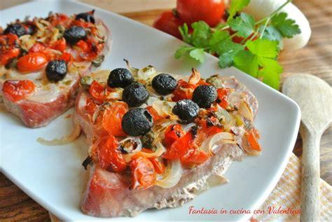 cucinare tranci di tonno fresco trancio di tonno con pomodorini cipolle e olive