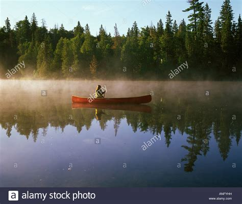 canoes in a fog lake superior woman in red canoe in early morning mist on a small lake