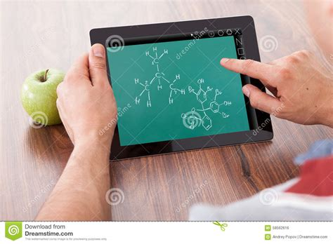 male architect with digital tablet studying plans in student studying chemical formulas on digital tablet stock