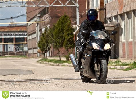 black motorcycle riding motorcycle rider with complete black stock photo